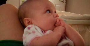 ребенок тянет кулак в рот.